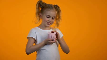 alfabetização : Smiling girl putting coin in piggybank and looking to camera, savings for future