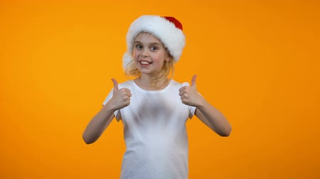 gesticulando : Smiling teen girl in santa hat showing thumbs up, christmas holiday preparations