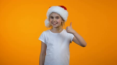 кампания : Funny girl in santa hat showing thumbs-us and winking, winter holiday sales