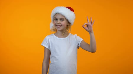 rekomendacja : Adorable teen girl in santa hat showing ok sign and smiling, recommendation