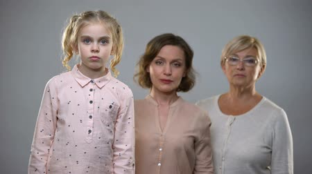 место : Sad daughter with mom and grandmother looking in camera, incomplete family