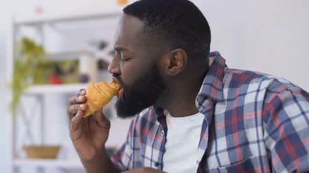 hassaslık : African american guy biting croissant and feeling toothpain, gum sensitivity