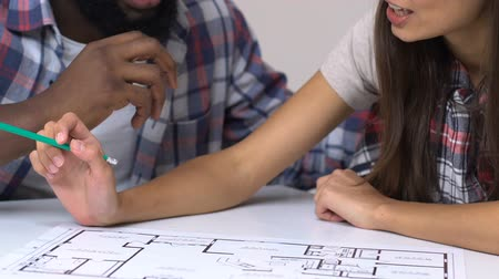 relocate : Happy couple looking at apartment project discussing purpose and design of rooms Stock Footage