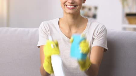 dezenfekte etmek : Cheerful woman holding detergent and washcloth, ready for apartment cleaning