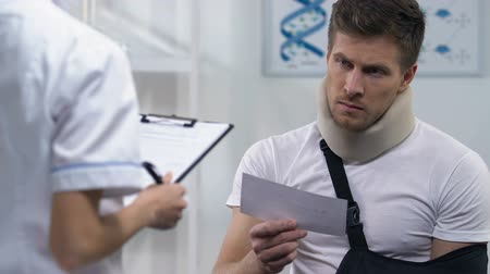 назначение : Doctor giving receipt to man in foam collar and arm sling, expensive treatment