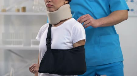 援助 : Doctor applying female patient in foam cervical collar arm sling, treatment