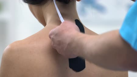фасонный : Doctor applying Y-shaped tapes on female upper back, reduce muscle tension
