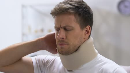 krk : Young man in foam cervical collar suddenly feeling sharp back pain, trauma Dostupné videozáznamy