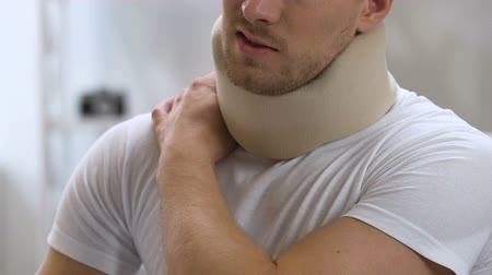воротник : Man wearing foam cervical collar suffering from pain in shoulder and neck Стоковые видеозаписи