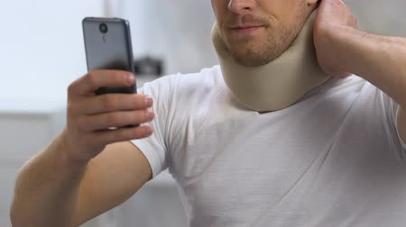 чувствовать : Man in foam cervical collar reading e-mail on phone suddenly feeling strong pain