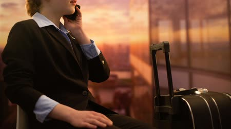 job transfer : Lady booking hotel by phone while waiting for flight at airport, business trip