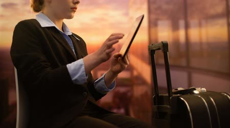 vliegticket : Woman booking hotel on tablet while waiting for flight at airport, business trip