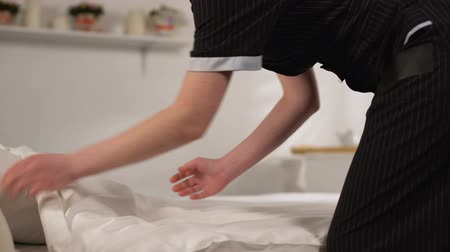 housekeeper : Housemaid in uniform making bed, tidying linens, high quality cleaning service Stock Footage
