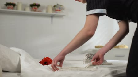 vendégszeretet : Young housemaid folding and taking towels away, cleaning hotel room for guests Stock mozgókép