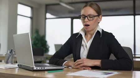 vyčerpání : Woman yawning while reading on laptop, tired of monotonous work in office