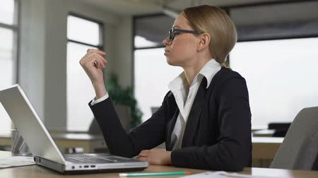 avoiding : Woman looking at nails from boredom at work in office, lack of motivation