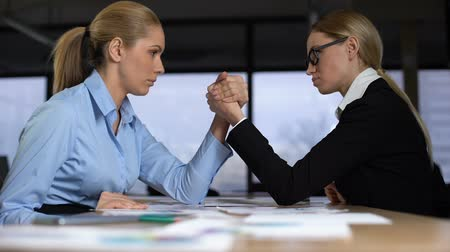 oposição : Two businesswomen doing arm wrestling in office, concept of rivalry at work Vídeos