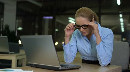 deterioration : Woman squinting eyes, taking off glasses while working on laptop, vision strain