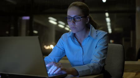 стремление : Pretty woman working on laptop late night in office, conscientious employee Стоковые видеозаписи
