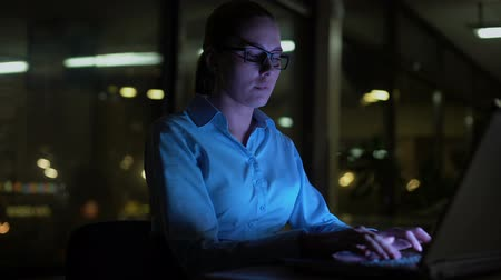 finanziere : Woman typing on laptop at night, working overhours in office, busy lifestyle