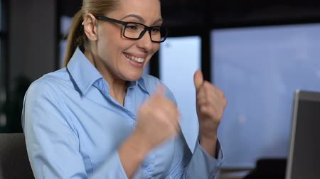 szám : Excited business lady showing yes gesture reading email on laptop, success Stock mozgókép