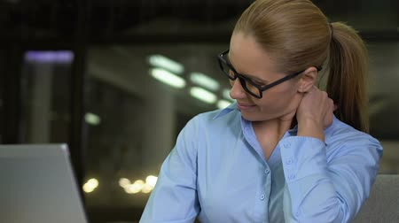 fájdalmas : Woman in business suit suffering neck pain, working office at night, health care