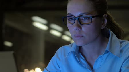 hardworking : Attractive business lady in eyeglasses typing laptop at night close-up, overtime