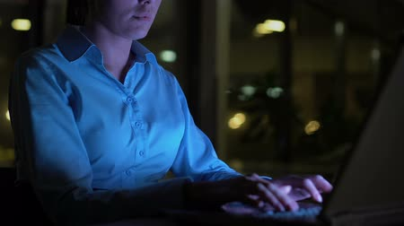 heures supplementaires : Business woman typing laptop at night in office, lighted by computer screen