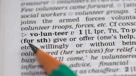 transcription : Volunteer word pointed in dictionary, doing or offering help without being paid