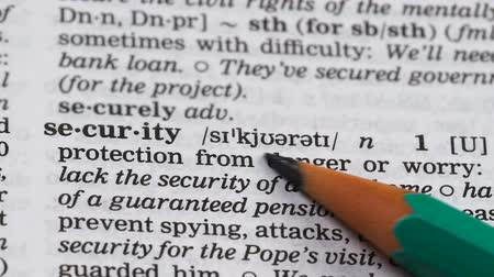 glossary : Security, pencil pointing word in dictionary, protection from danger, internet Stock Footage