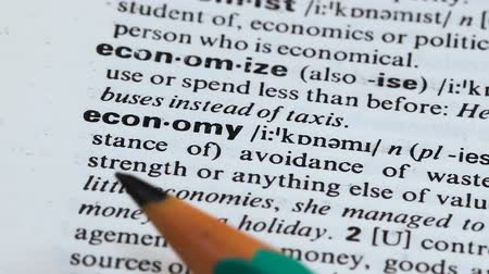 книжный магазин : Economy word meaning in dictionary, avoiding of wasting resources, planning Стоковые видеозаписи