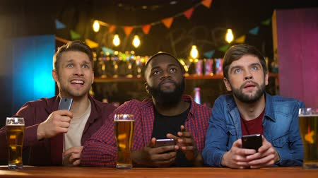 yargı : Multiethnic male friends watching football match in pub, upset with team losing Stok Video