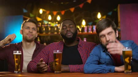 basketball : Anxious multiethnic friends unhappy, favorite team losing match, time in pub Stock Footage