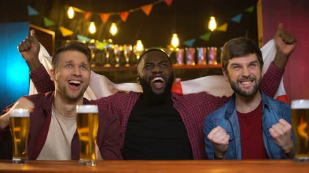 multiethnic : Cheerful multiracial fans cheering for football team, waving english flag, hobby Stock Footage