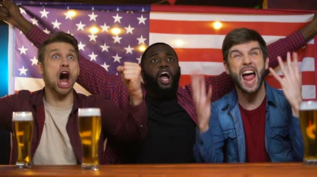賭け : American multiethnic male fans celebrating favorite team victory, waving flag 動画素材