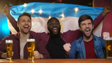 eredmény : Emotional black and caucasian men cheering for argentinian football team.