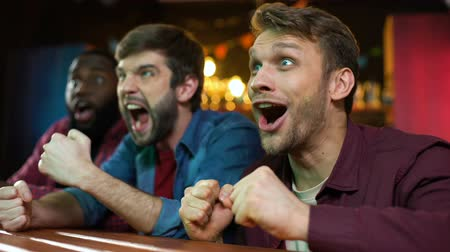 gesticulando : Multiracial fans celebrating favorite team scoring goal, watching game in pub