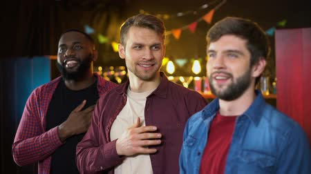beisebol : Multiethnic friends listening to anthem before soccer match, results time in pub Stock Footage