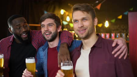 multiethnic : Smiling drunk football fans celebrating victory in championship, results time