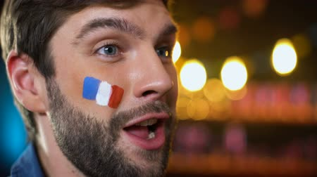 french team : Happy handsome bearded french fan with painted flag on cheek celebrating goal