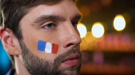 french team : Anxious french fan with painted flag on cheek making facepalm, disappointment