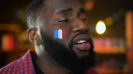 french team : Black french football supporter with flag on cheek unhappy with team failure