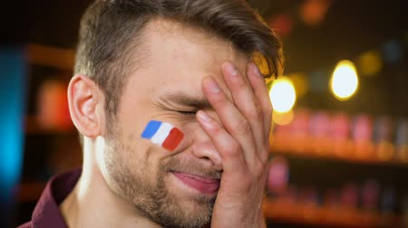gesticulando : Upset bearded football fan with french flag on cheek making facepalm team losing