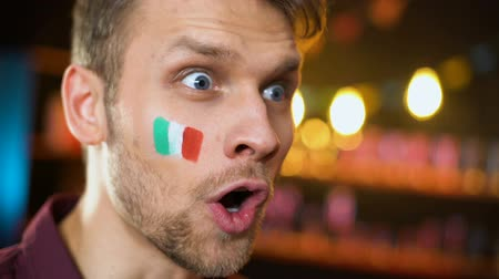 gesticulando : Cheerful italian fan with flag painted on cheek shouting, team scoring goal