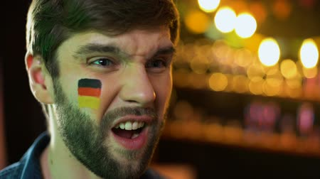 facepalm : Unhappy male with german flag painted on cheek making facepalm, team losing game