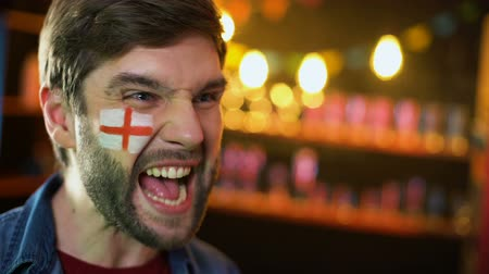 gesticulando : Joyful english football fan with flag on cheek making yes gesture, team winning