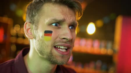 gesticulando : Disappointed male fan with german flag painted on cheek waving hand, failure