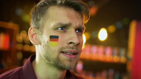 gesticulando : Joyful german football fan with flag on cheek happy for team scoring goal, win Vídeos