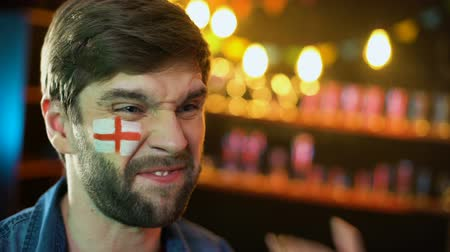 gesticulando : Displeased male football fan with english flag on cheek making facepalm gesture