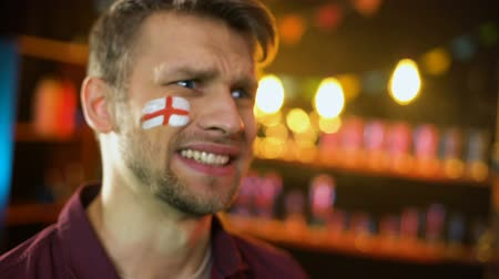yargı : Fan with english flag painted on cheek unhappy with team losing match, failure Stok Video